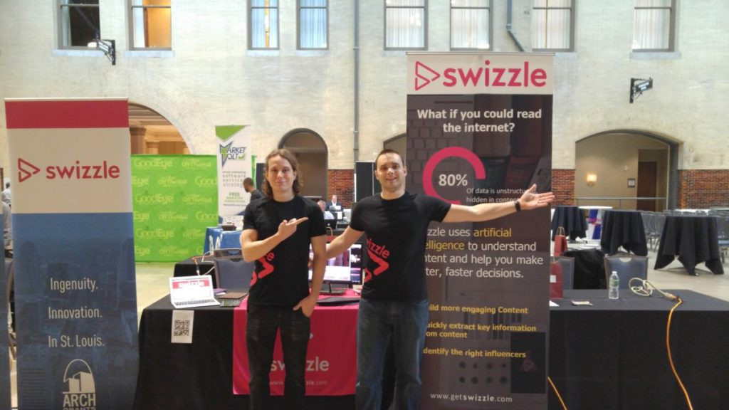 Members of the Swizzle team at a booth at MDMC. Grey Geppert, Data Strategist on the left, Nick Szabo, COO on the right.
