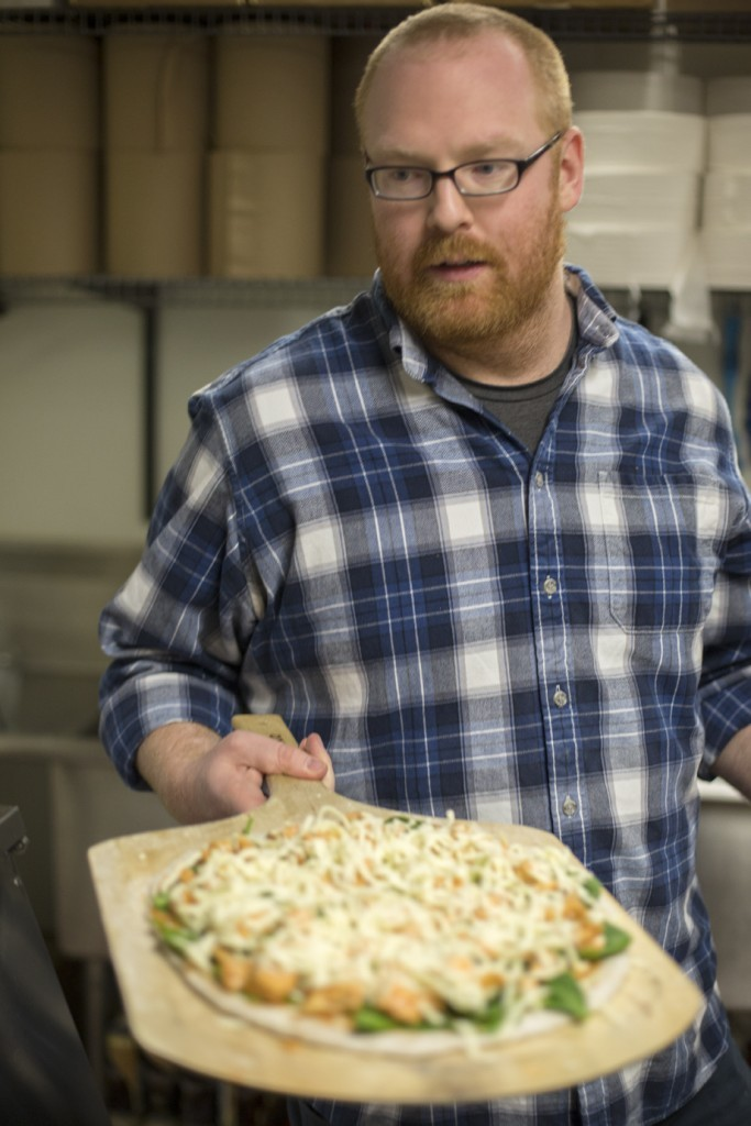 Arch Grants recipient Jonathan Leek puts a pizza into an oven at Orbit Pinball Lounge. His company, Pulse Pizza serves pizzas made with spent beer grains. Photo courtesy of Missouri S&T .