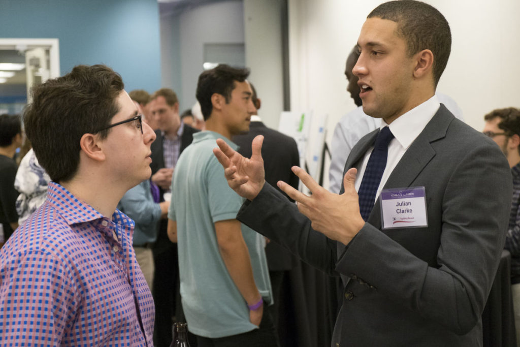 Julian Clarke of SpideySense explains his startup to a participant at Demo Day, held April 25 at Cortex.   Demo Day photo: Sid Hastings/Washington University